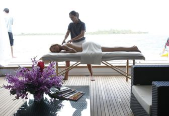 charter guest enjoys a massage in the beach club aboard luxury yacht SOVEREIGN
