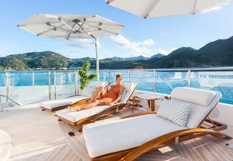 female guest unwinds on a sun lounger on the sundeck of luxury yacht 'King Baby'