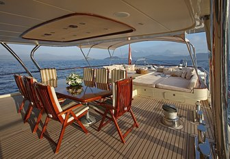 covered alfresco dining area with sunpads beyond on the aft deck of superyacht DAIMA
