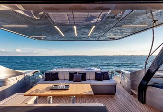 Open air dining area and sofa on motor yacht BEYOND with sea in background