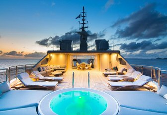 Sunloungers on deck of O'MEGA superyacht with soft lighting at sunset