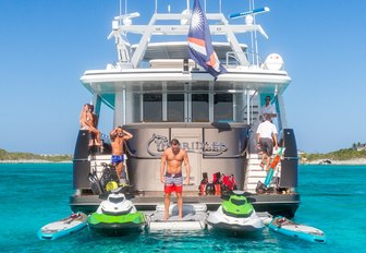 guests hang out alongside water toys on the swim platform of luxury yacht UNBRIDLED