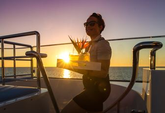 Crew member at sunset carry drink