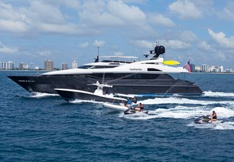 motor yacht Temptation cuts through water with water toys on a charter vacation