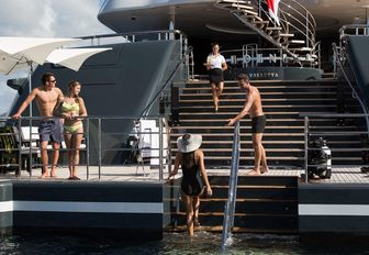 charter guests gather on the large swim platform of luxury yacht PHOENIX 2