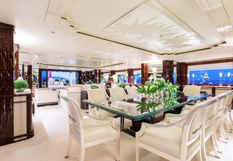 glass topped table forms formal dining area in main salon of charter yacht 'Lioness V'