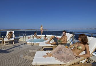 Guests on O'MEGA superyacht. Three people on sunloungers talking and three around jacuzzi