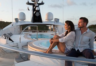 charter guests relax near the Jacuzzi on the sundeck of superyacht PHOENIX 2