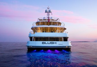 view of stern on motor yacht BLUSH as the sun sets over the horizon