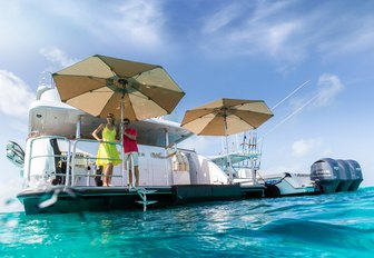 charter guests stand on the umbrella-shaded swim platform of motor yacht Remember When