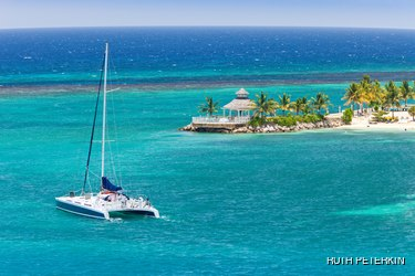Sailboat on turquoise sea and beautiful beach with palm trees in the background