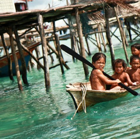 Poor children floating on the sea near to the beach hut