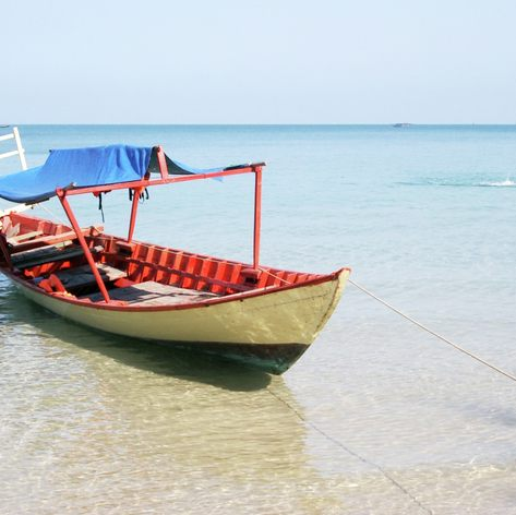 Simple, colourful boat moored at the shore