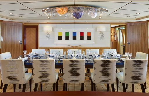Bright dining room on Victoria Del Mar with 12 seats around a table and large chandelier above