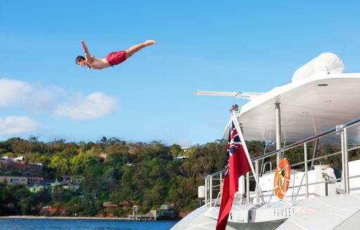 man dives into water from the deck of a luxury superyacht