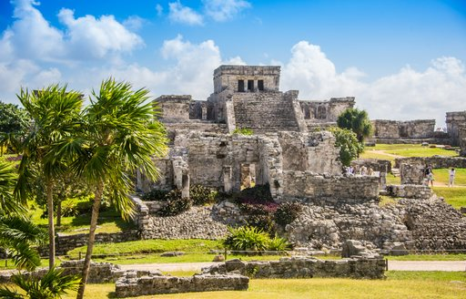 mayan ruins in mexico, with palm trees in foreground