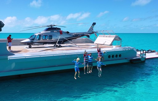 charter guests jump off the deck of luxury yacht BOLD
