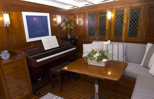 piano and sofas in the main salon aboard charter yacht EROS