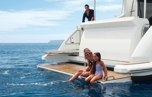 family relax on swim platform of luxury crewed yacht