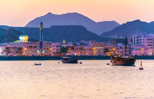oman port by night, little wooden boats with mountain backdrop