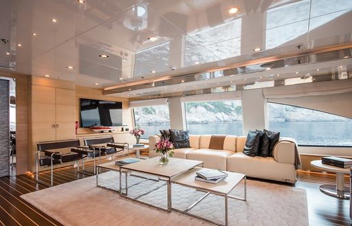 Comfortable interior of superyacht ARBEMA, with cream sofas, large windows and flatscreen TV on wall