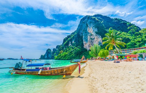 little wooden boat on the sand in south east asia, with mountain backdrop