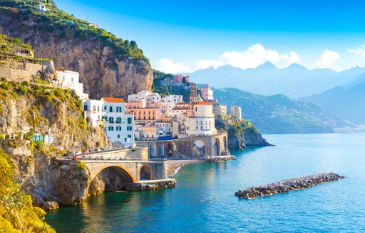 the  buildings of the amalfi coast nestled in the crevices of cliffs and hilltops with beautiful mountains in the background a perfect anchorage for guests on a superyacht looking to explore while on their italy yacht charter vacation