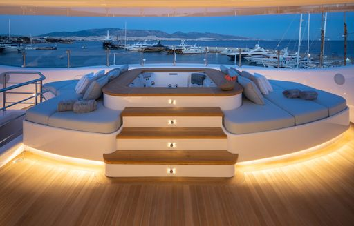 Wooden steps leading up to Jacuzzi and sunpads on superyacht O'PARI