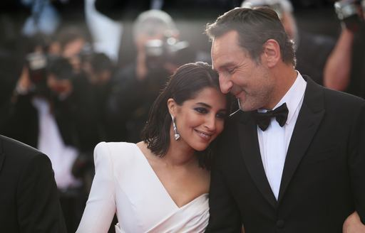 actress wearing white lays her head on shoulder of actor at cannes film festival