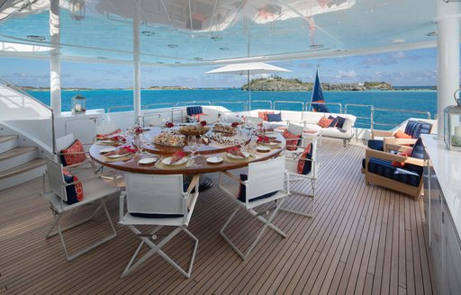 a circular dining table located in the lower aft deck of charter yacht time for us