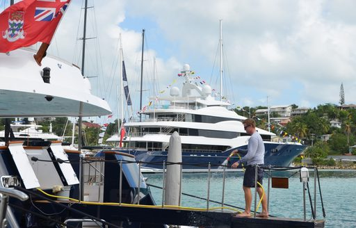 crew member walks onto yacht with superyacht AMARYLLIS in the background in Antigua