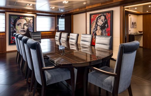 Formal dining table with unusual artwork behind on walls of superyacht RARITY