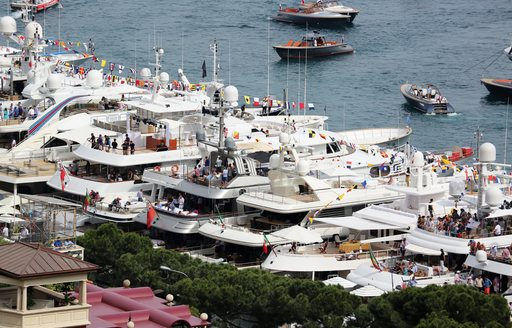 Row of superyachts moored at Monaco Grand Prix, flocks of guests on each yacht enjoying party atmosphere.