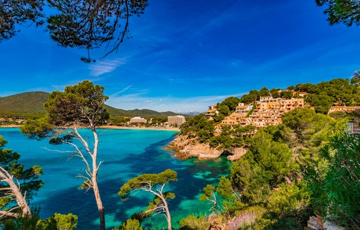 Town on hill of cliff in the Balearic Islands, with bright blue water and pine trees