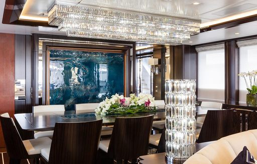 Lady Li superyacht dining set-up, with artwork on the wall and crystal chandelier on the ceiling