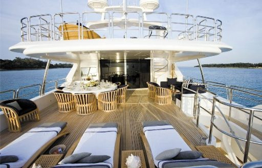 sun loungers and dining table on the upper deck aft of charter yacht SEABLUE'Z