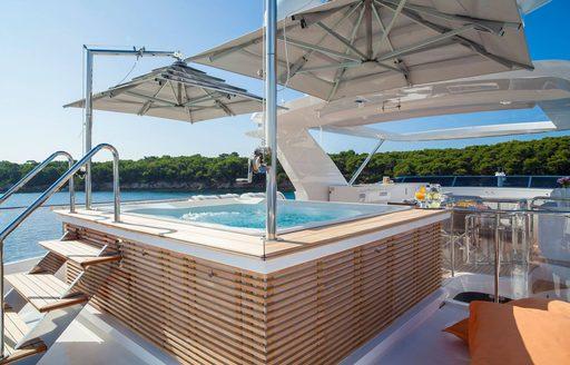 spa pool with umbrellas overhead on the sundeck of luxury yacht DYNAR