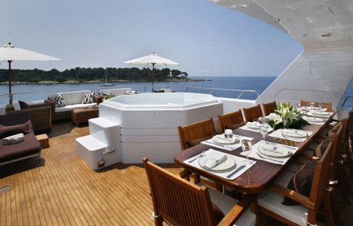 Sundeck dining area and jacuzzi on charter yacht daydream