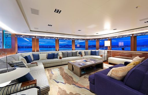 observation lounge with comfortable sofas and sweeping views aboard charter yacht Planet Nine