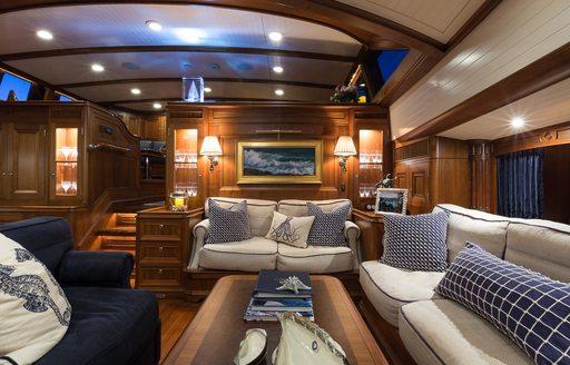 beautiful walnut lower salon with lounge area on board charter yacht MARAE