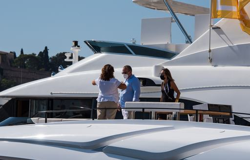 Visitors with masks view a yacht in-show at the MYS 2021