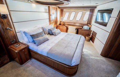 owners suite on luxury superyacht chess, with large double bed and wide windows