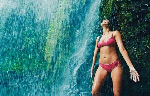 A woman in a bikini standing below a running waterfall