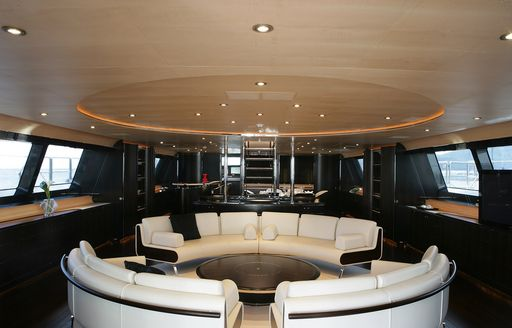 Main salon onboard Parsifal III, central curved sofas facing each other around a coffee table with windows across both sides