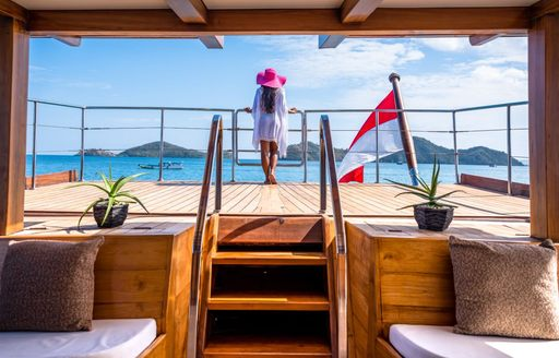 Charter guest stands on superyacht LAMIMA
