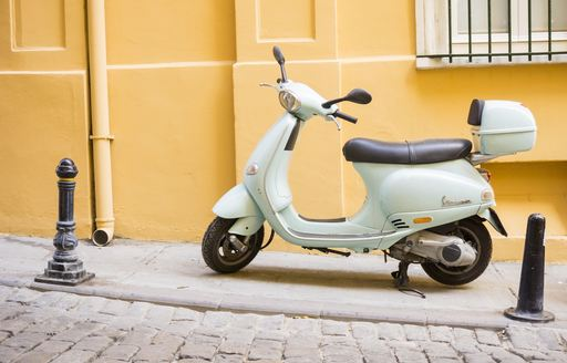 a white vespa against the yellow coated wall of an Italian boutique in naples where guests of a luxury charter yacht are perusing for some new designer clothes