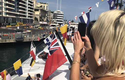 cars on circuit during monaco grand prix as seen from a luxury yacht