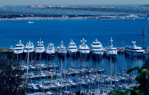 Superyachts lined up beyond smaller yachts in Cannes harbour