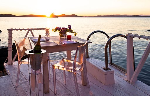 table set for two at Phi Beach, Sardinia, as sun sets