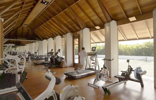 A man runs on a treadmill inside an enormous gymnasium housed inside of a wooden structure